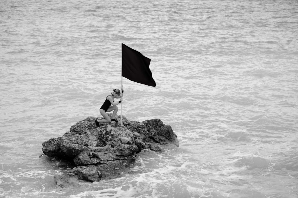 A psychologically resilient female swimmer embraces adversity as she swims to a rock and plants a flag.