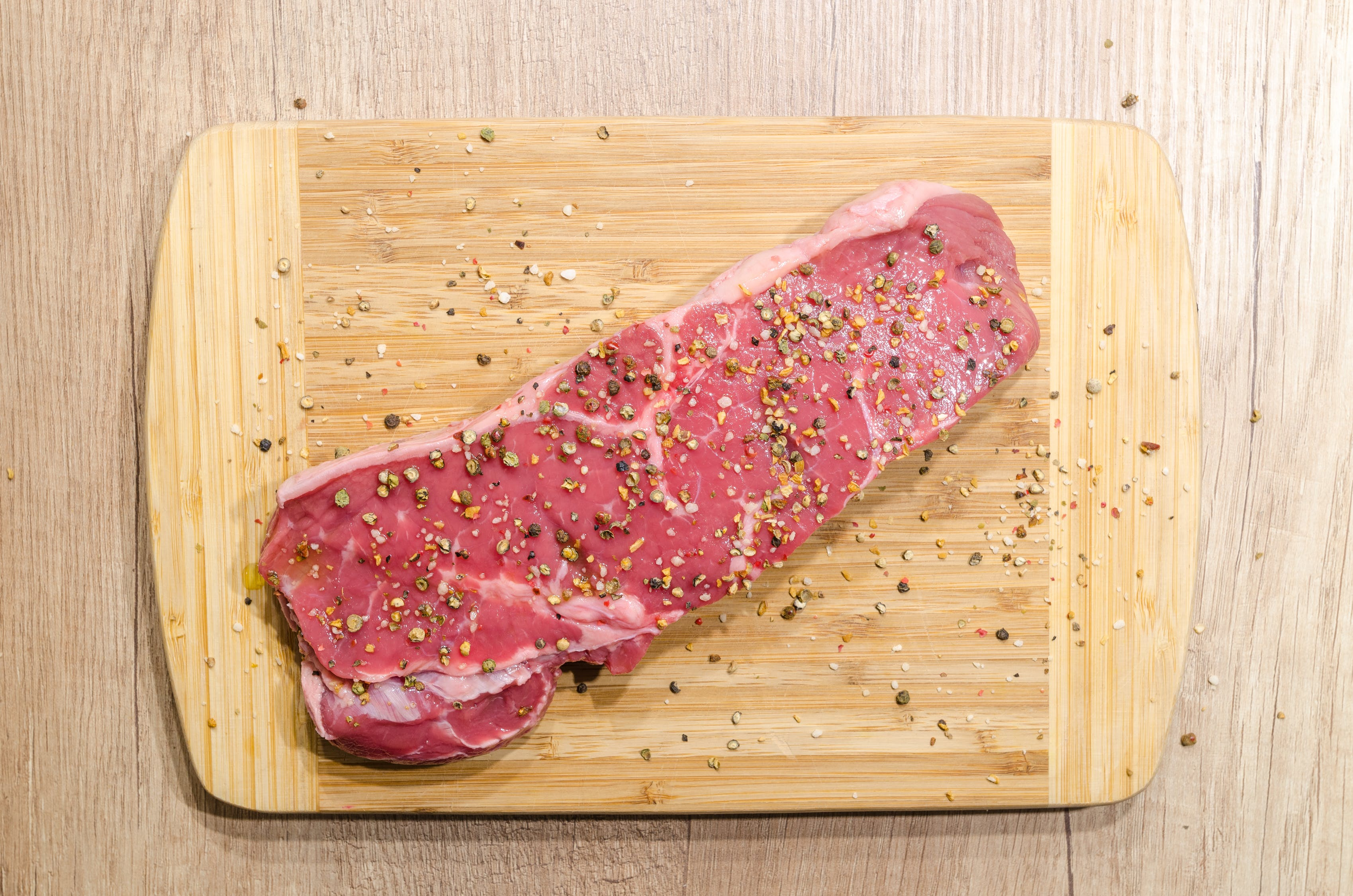 A cut of lean beef on a cutting board with seasonings.