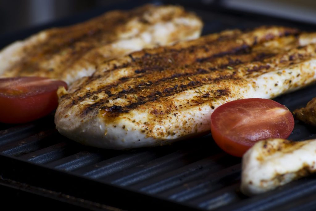 Chicken being grilled with tomatoes.