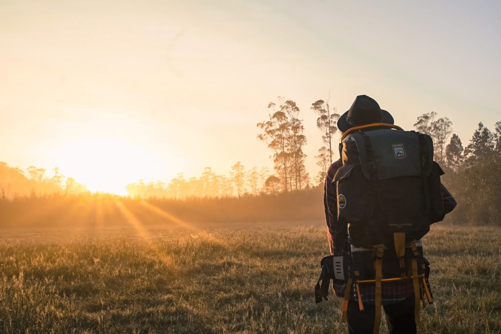 A backpacker walking across a grassy meadow into the sunset.