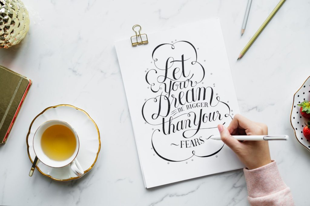 "A woman writing ""Let your dreams be bigger than your fears"" beautifully beside a cup of tea."
