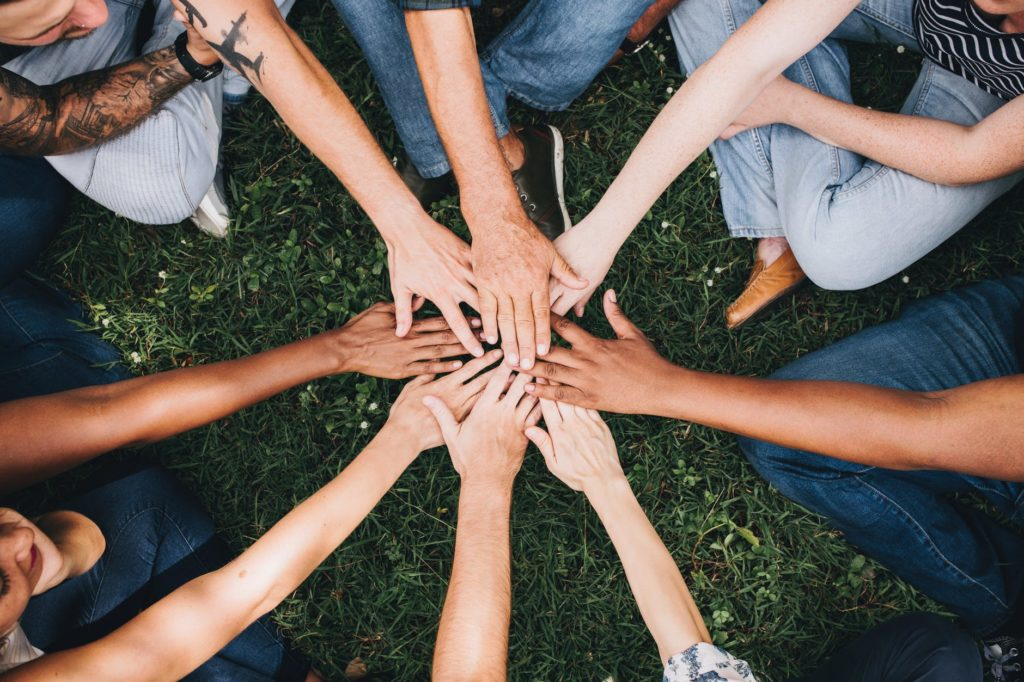 A group of friends all putting their hands together to show unity and support.