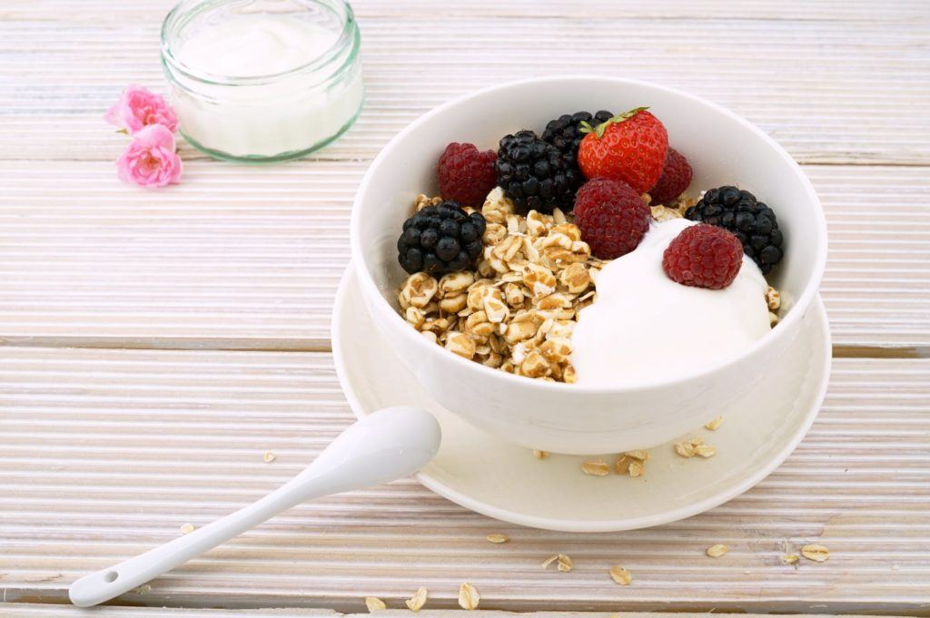 A Greek yogurt parfait containing oats, raspberries, blackberries, and a strawberry. Greek yogurt is just one of the excellent protein sources here.